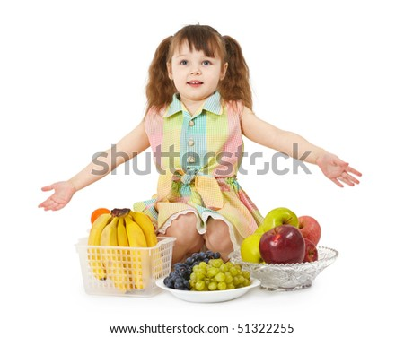 A little girl with a big heap of different fruits on white background - stock photo