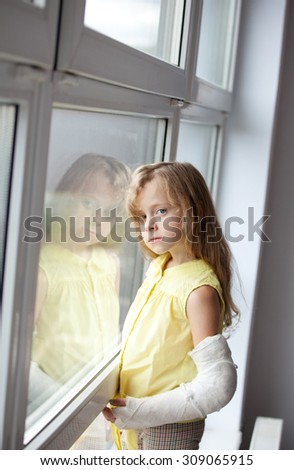 a little girl with a broken arm , window