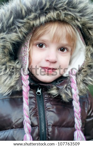 A little girl with a hood on his head - stock photo