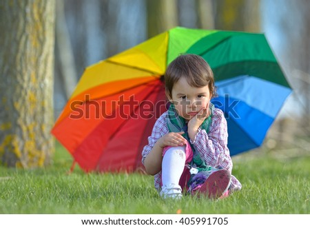 A little girl with a rainbow umbrella in forest - stock photo