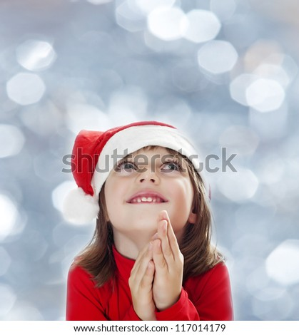 a little girl with a santa cap wishing something - stock photo