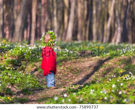 A little girl with a wreath in spring forest - stock photo