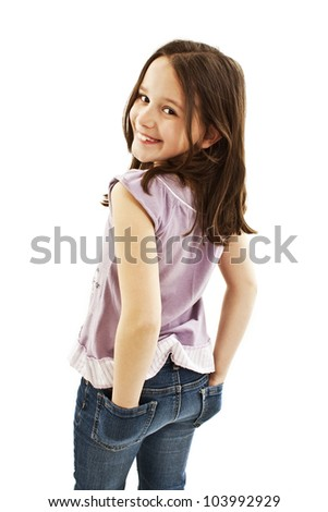 A little girl with hands in jeans pockets over white background.
