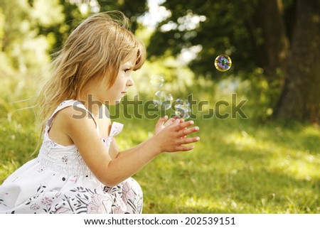 a little girl with soap bubbles