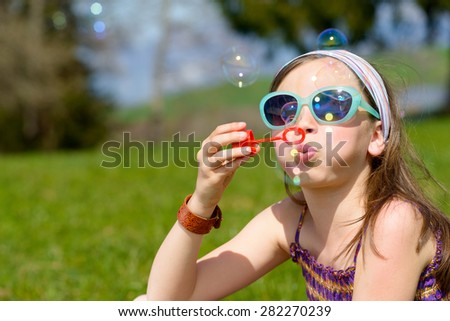 a little girl with sunglasses making soap bubbles - stock photo