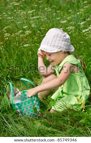 A little girl with the kitten for a walk on the lawn - stock photo