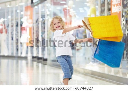A little girl with the packages in the shop - stock photo