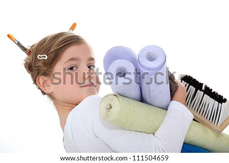 A little girl with wallpaper rolls. - stock photo