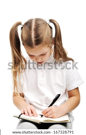 A little girl writing in a notebook in studio.