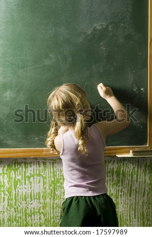 A little girl writing on a chalkboard.  Her back is to the camera.  Vertically framed shot. - stock photo