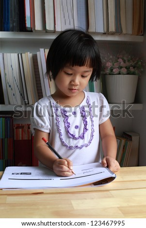A little girl writing or drawing on wooden table.