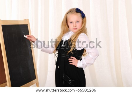 A little girl wrote a white chalk on a blackboard. - stock photo