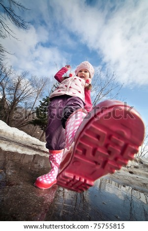 A little girls in pink boots splashing in a muddy puddle - stock photo
