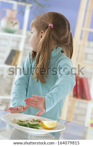 A little girls refusing food, kid does not want to eat turning back - stock photo
