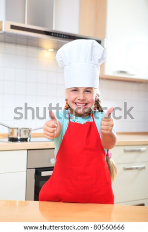a little junior cook showing her thumbs up - stock photo