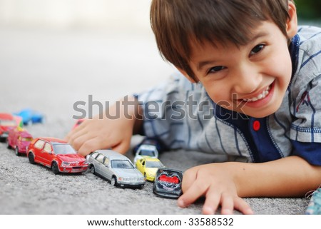 A little kid is laying and playing with cars - stock photo