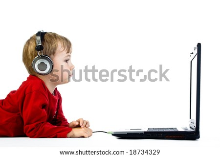 A little kid wearing a headphone watching a movie on his laptop, on a white background.