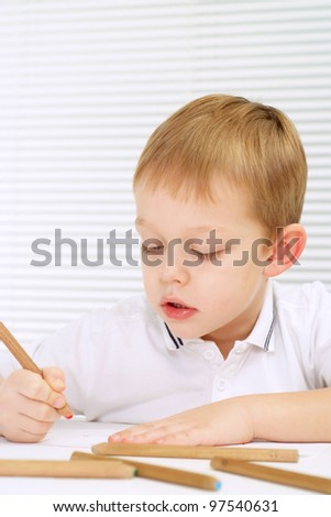 A little lad sitting at a table with a pencil on a light background - stock photo