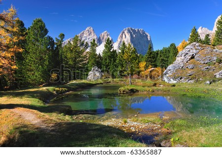 A little lake in a forest on a day in autumn. The mountain in the back named langkofel belongs to the Dolomite Alps.