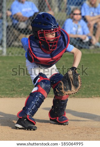 A Little League Catcher Going for a Wild Pitch Behind the Plate - stock photo