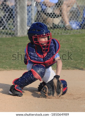 A Little League Catcher Going for a Wild Pitch in the Dirt - stock photo