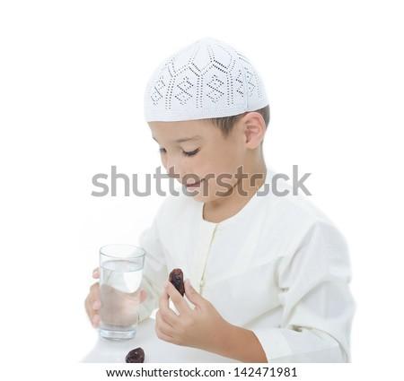 A little muslim boy wearing islamic attire ready for braking Ramadan fast - stock photo