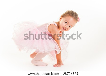 A little pink ballerina in  a playful mood in the studio. - stock photo