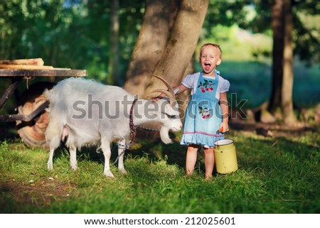 A little pretty blond girl in a white dress and blue apron holding a milk-can and playing with her pet goat in the field in a sunny summer day. Kids as helpers in the country. - stock photo