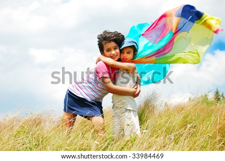 A little pretty girl and boy with scarf above head on meadow