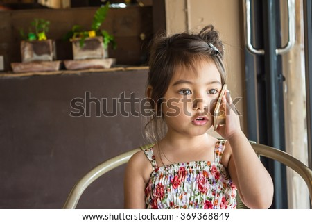 A little pretty girl mimicking her mom talking on cellphone by using a small piece of wood  - stock photo