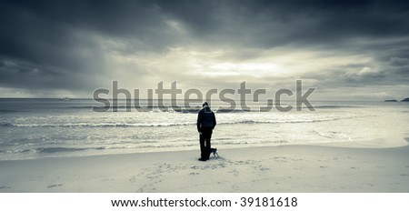 A little puppy with his master along a winter sea's shore. Duotone image in cinematic view - stock photo