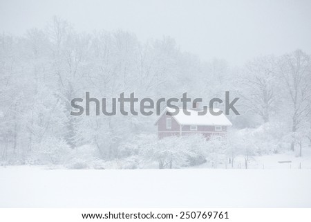 A little red cottage in snowy winter weather