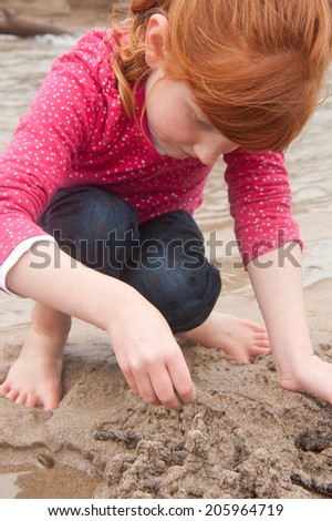 A little red haired girl building a sand castle witn wet sand beside a tidal river lagoon at a New Zealand surf beach - stock photo