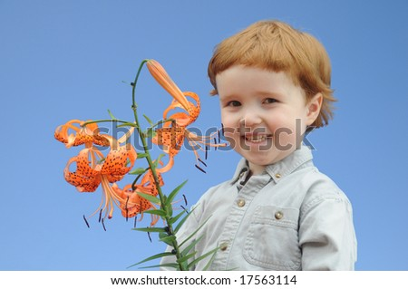 A little red-headed boy holds up orange sultan cap flowers against a blue sky. - stock photo