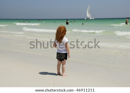 A little red headed girl with ringlets in her hair watching the sailboat pass by on the emerald beach in Florida.