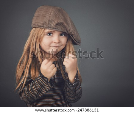 A little retro girl with a hat has her fists up and looks strong and tough on a gray background for a safety or strength concept. - stock photo
