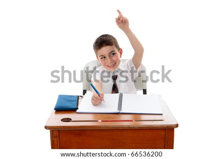 A little school boy student sitting at desk and with one hand up to answer or ask a question.  White background. - stock photo