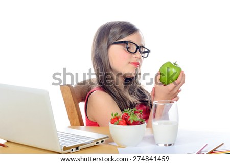 a little school girl looks apple on her desk - stock photo