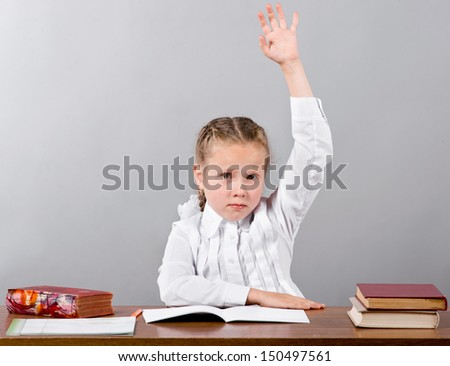 A little schoolgirl sitting by the desk raising her arm signaling that she know and is ready to answer - stock photo