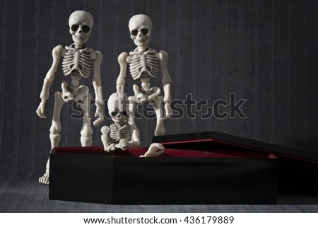 A little skeleton kneeling and praying at the coffin - stock photo