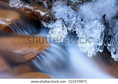 A little stream covered with ice - stock photo
