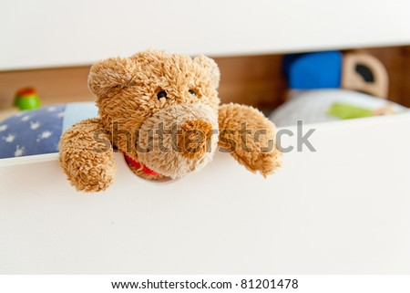 A little Teddy looking out of his drawer with some more toys in the background - stock photo