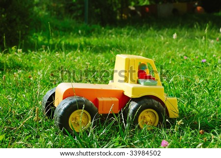 A little truck toy laying in the grass