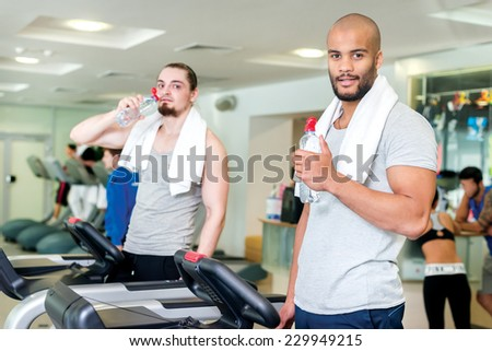 A little water in training. Two confident athlete in training in the cardio room holding a water bottle in hand. Two athletes engaged on Treadmill gym - stock photo