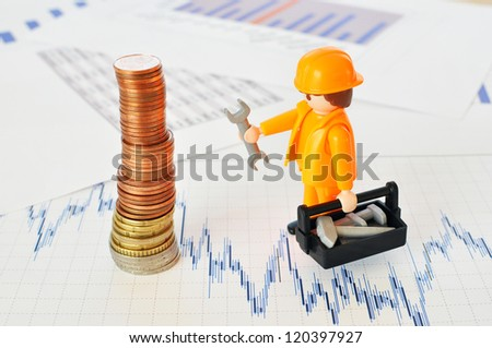 A little worker at a pyramid of coins against financial reports