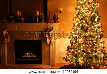A living room at Christmastime lit only by the fire and Christmas tree. - stock photo