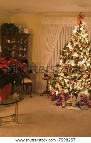 A  living room lit by the glow of the Christmas tree.  Long exposure produced star like tree lights. - stock photo
