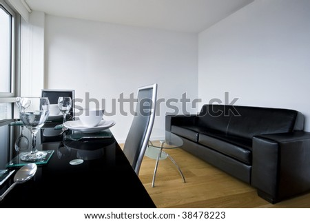 a living room, lounge with a black glass top table and diner set up. - stock photo