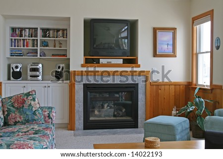 A living room with a fireplace and Television, DVD player - stock photo