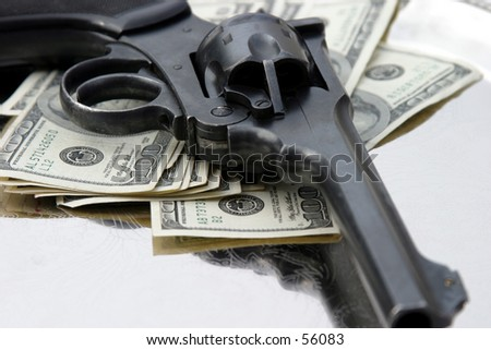 a loaded 45. cal pistol lays upon a pile of cash sitting on a silver tray